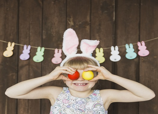 playful-girl-in-bunny-ears-with-eggs